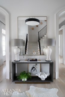 Simplified architecture allows the lighting and art to shine, says Amtower. Black and brass combine in the front foyer, including the round chandelier from Arteriors, custom floating mirror from Grey and pin brass candlesticks from R Hughes.