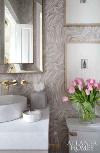 The designer often brings in pattern with wallpaper, such as the marbling design by Zoffany through Grizzel & Mann layered with a mirror by Restoration Hardware. The arrowhead art is by Max & Company.