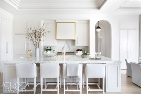 The cabinetry by Atlanta's Best Cabinets—who selected Neolith countertops in the kitchen—echo Shawn Amtower's streamlined approach. The custom stools by Bjork Studio are upholstered in a Joseph Noble faux leather. The custom hardware is by DLV Designs and the pendant is from Circa Lighting.