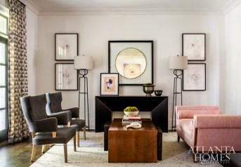 In the sitting room, a chaise lounge in coral herringbone fabric and a pair of linen-covered vintage wing chairs surround a walnut table from Holland Macrae. The console table is by Skylar Morgan.