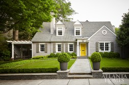 American boxwoods line the newly manicured front lawn. The fiber cement planters are by Greenform.