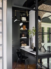 Outfitted with black cabinetry by Design Galleria Kitchen and Bath Studio and illuminated by a midcentury modern-inspired brass chandelier from Circa Lighting, the wife's office blends classic and contemporary elements.