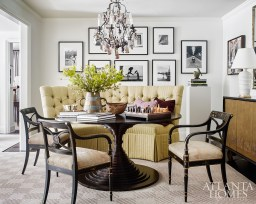 An artful Hélène Aumont table through R Hughes commands the dining room. Its striking lines are softened by a custom Bungalow Classic banquette and the homeowners' own Regency-style chairs. The gallery wall features black-and-white photography by Henri Cartier-Bresson and Édouard Boubat.