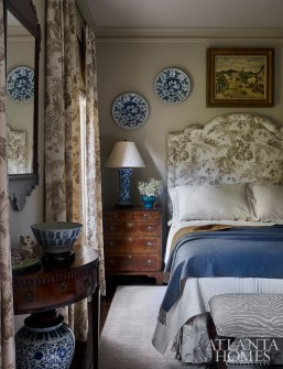 In the guest bedroom, he selected a lively floral-patterned fabric by Scalamandré and scattered blue-and-white porcelain throughout. The collectibles rest on stands and read like sculptures in the other guest bedroom and the draperies made from Fabricut's Float Ikat provide a little modern zip to the decor.