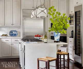 The homeowners wanted a kitchen that balances function with classic style. The result: a clean sweep of Carrara marble cut into herringbone tiles for the backsplash and applied as simple slabs on the countertops with a waterfall edge wrapping the island. Circa Lighting's English-inspired fixture hangs overhead.
