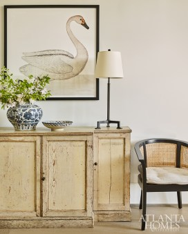 Webb extended her use of softly-toned woods into the music room, where a late 19th-century English buffet is joined by a modern caned chair from Bungalow Classic.