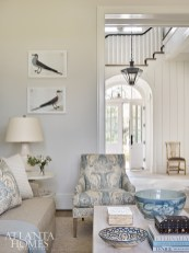 To cozy up the music room, Webb employed patterned fabrics and watery shades of blue. A Rosa Bernal linen fabric, available through Travis & Company, covers the chair and sofa pillow. The vintage blue bowls and ceramic lamp are from Bungalow Classic.