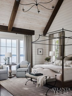 Light and airy is the idea in the master suite, where grasscloth-covered nightstands flank a wood and iron four-poster bed with an upholstered headboard. The blue swivel chairs are from WebbMarsteller.