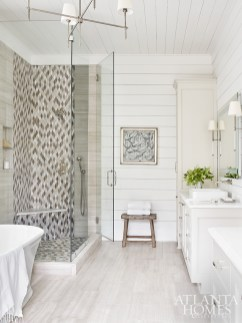A water-jet glass mosaic shower tile complements the brushed limestone flooring from Renaissance Tile & Bath in the master bathroom. The bench is from B.D. Jeffries.