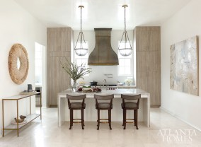 Polished nickel, distinctive pewter and elegant brass mix effortlessly in the kitchen amongst the custom hood and waterfall island. The island was built to accommodate a crowd; the original abstract artwork by Paige Kalena Follmann commands their attention.