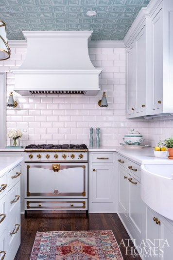The jewel-box air is fully complete with a wallpapered eiling, pale-blue cabinetry and gleaming brass accents, visible on the La Cornue range.