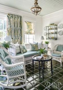 Designer Mallory Mathison Glenn used the sunroom's original mid-century glazed tile floors as inspiration for the space's blue-green scheme. The large-scale Cowtan & Tout fern print rejuvenates the antique wicker.