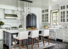 """Custom polished-nickel hardware, a deep gray-lacquered island and a glass fixture created by artist John Pomp reflect light—casting the kitchen with a subtle shimmer and, as Bromenschenkel describes, a hint of sexiness when night falls and lights are dimmed. """"The shiny materials created this narrative that yes, it's a beautiful classic kitchen, but it also has a contemporary kick to it."""""""