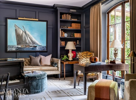 """The library takes a masculine turn with tufted seating and rich blue-gray walls painted in Benjamin Moore's Witching Hour. The desk chair came from Bromenschenkel's grandfather's home in Holland. """"It was a family piece that I wanted to give a new chapter, so I reupholstered it in Scalamandré's Tiger velvet and placed it in the library."""""""