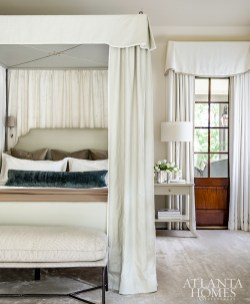 """In the master bedroom, Bromenschenkel created a """"room within a room"""" by using glazed linens in a soft palette on a canopy bed, emulating the sanctuary-like environment she desired. """"When you walk in, the quietness envelops you and it's like you're putting a pause on life."""""""