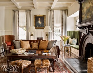 An antique camel hair rug from Moattar grounds a custom leather sofa and reproduction coffee table in the formal living room. The draperies are an ivory Schumacher linen with embroidered Samuel & Sons trim through Ainsworth-Noah.