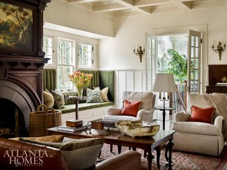Designed to blend in with the home's original woodwork, the custom mantel elevates the brick fireplace in the formal living room. The antique French bronze sconces are from Lamp Arts Inc.