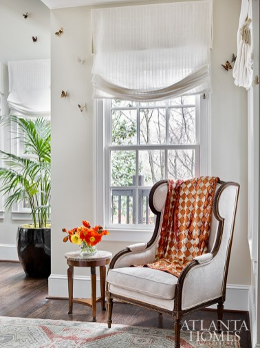 Re-covered in an ivory velvet from Schumacher, an antique French carved chair from Foxglove Antiques & Galleries is a relaxing spot to enjoy the solarium's natural daylight.