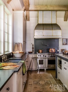 The custom pewter hood with brass banding, designed by Dixon, leans into the industrial vibe of the well- appointed kitchen.