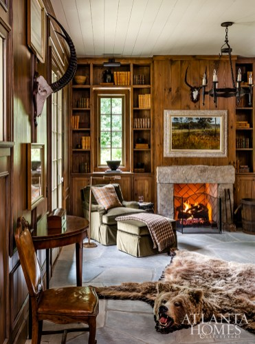 A three-piece stone fireplace mantel and Crab Orchard stone flooring complement the pine wall paneling in the den.