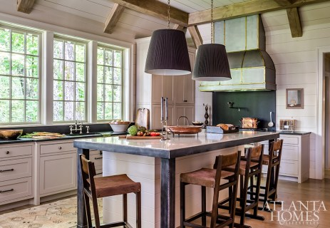 Pendants with pleated fabric shades soften the masculine-leaning kitchen, which includes a custom marble-topped island with iron legs and banding. The barstools with cowhide seats are from R Hughes.