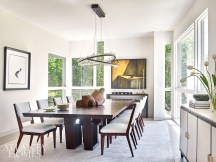A custom rock crystal chandelier by Christopher Boots from R Hughes illuminates an expandable wooden table by Hellman-Chang in the formal dining room.