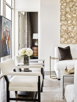 Upholstered in white linen, twin chairs and a pair of cloudlike sofas, all from Lee Industries, allow the panoramic 18th-floor views and artwork to take center stage.