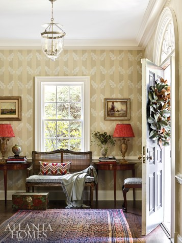 Designer Margaret Kirkland created an elegant seating area in the entry with an antique caned bench. Decorative painter Brian Carter customized Christopher Norman wallpaper with hand-painted leaves.