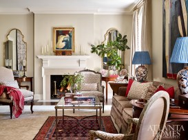 In the living room, Kirkland flanked the fireplace with antique demilune tables and mirrors from Parc Monceau to create a sense of symmetry. To preserve the sofa, originally from the 1940s, the design team added a trim and taller legs and kept the original upholstery.