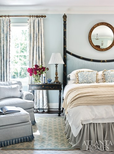 To create a sense of calm in the main bedroom, Kirkland ensconced the space in a soft blue, with a pale pink ceiling and antique tole chandelier from David Skinner Antiques & Period Lighting. The bed linens are from Leontine Linens, the mirror is from Huff Harrington Home and the rug is Keivan Woven Arts.