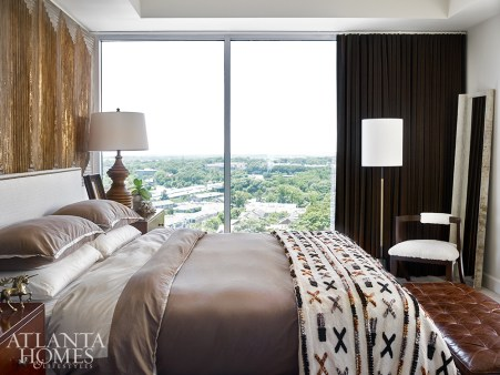 A blanket from CB2 adds a punch of pattern to the upholstered bed in the master suite.