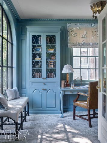 The study's blue-green paint color, Farrow & Ball Card Room Green, was inspired by a similarly hued roman shade fabric. Built-in cabinetry cleverly conceals a cigar humidor and liquor cabinet.