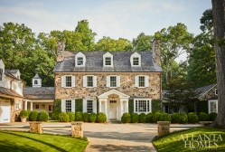 Native fieldstone on the front façade lends a handsome presence; the house was designed by D. Stanley Dixon. Boxwood frames the house and softens the motor court.