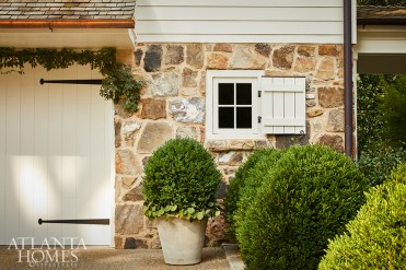 Hearty boxwoods soften and brighten the native fieldstone.