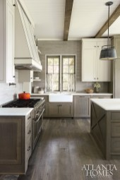 Layers of subtle color and texture give the kitchen warmth. Base oak cabinets are stained soft gray to allow the wood grain to show through. Upper cabinets are painted Sherwin-Williams Repose Gray for a slight variation in finishes. Zinc strappings on the hood introduce another element while complementing the gray tones.