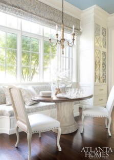 An oval Louis XVI table with a walnut top by Dennis & Leen surrounded by a built-in banquette and chairs by Hickory Chair offers a spot for casual meals in the spacious kitchen.