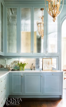 Painted in Oval Room Blue by Farrow & Ball and accented with antiqued mirror, the butler's pantry is both stylish and functional. The brass fixture is by Paul Ferrante.