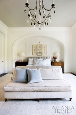 Recessed into a niche and covered in tufted Scalamandré satin, the upholstered bed coordinates perfectly with an elegant armless sofa by Suzanne Kasler for Hickory Chair.