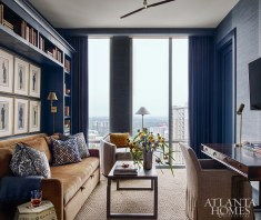 A navy grasscloth wallcovering by Phillip Jeffries creates a more masculine feeling in the den, where the husband often works at the oak desk by Julian Chichester.