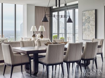 Purchased by the owners during one of their annual trips to Nantucket, a black metal chandelier illuminates a contemporary wooden dining table and upholstered chairs from Hickory Chair. The artwork is by Jylian Gustlin.