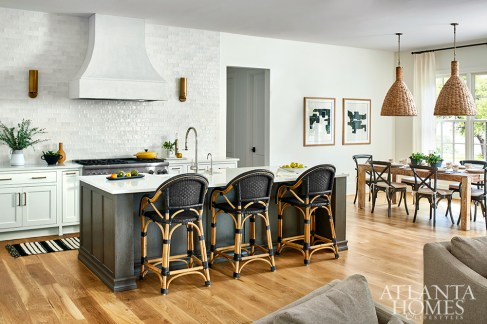 The kitchen—which features pendant lights from RH and a hood from Artistic Artisans—provides multiple seating areas for both family and guests.