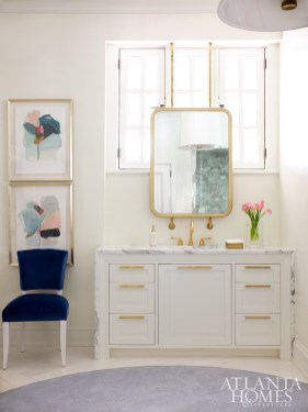 Adorned with a marble waterfall edge, a vanity from Karpaty makes a handsome addition to the newly renovated master bathroom.