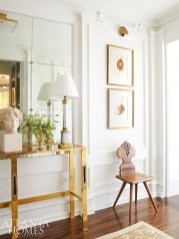 In the entryway, a wall of antique glass greets the couple, as do treasures, like the brass table and antique chair, collected on their buying trips to Europe. The artwork is by French artist Jean-Pierre Bourquin, represented by TEW Galleries.
