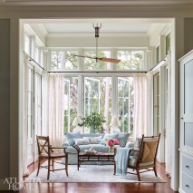 An airy sunroom provides a spot for reading and relaxation, while a small dining table behind the sofa provides a casual setting for evening dinners.