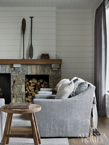Gray seating, a stone fireplace and wooden accents are a cozy welcome in the guest corridor's living room.