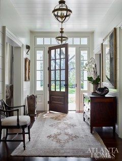 An antique rug anchors the entry, as does an antique chair upholstered in a Rose Tarlow fabric. The light fixtures are by Circa Lighting.