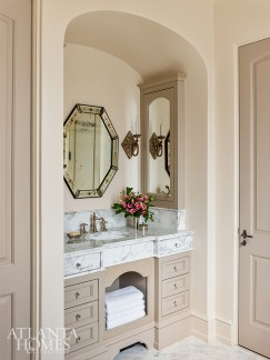 A recessed vanity with facing side medicine cabinets and a marble top with integrated top drawers tells a fresh story while still feeling classic. The Venetian mirror is from Robuck.