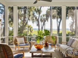 The back porch—which overlooks the marsh and is the perfect vantage point for sunrise views—features cane seating from Gloster, upholstered in performance fabric by Perennials (on the sofa) and Kravet (on the armchairs). The zinc coffee table is Mr. Brown London.