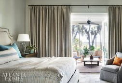 The primary bedroom opens up onto the back porch; Wilkins created a sense of refuge through calming hues. The drapery fabric is Cowtan & Tout and the bedding is custom through Legacy Home. The armchair is Charles Stewart, the bedside lamp is Visual Comfort and the nightstand is Hickory White.