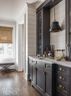 Stained cabinetry and a rustic pendant from Currey & Company create a handsome wet bar area that's perfect for entertaining
